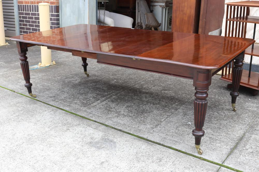 Antique mahogany extension dining table with two leaves, standing on turned fluted legs, with replacement brass castors, approx 78cm H x 393cm W (with leaves) x 120cm D