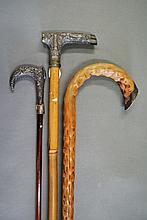 Three walking canes, one with Indian silver