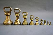 Set of nine antique brass graduating bell weights.