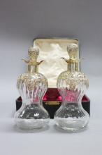 Antique boxed pair of decanters, hour glass form mounted with chased silver collars and stoppers. Box Marked Weir & Sons Dublin Ireland. Marks to collar rubbed, touch marks to stoppers legible, approx 21cm H