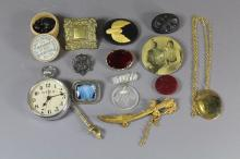 Costume jewellery lot to include a bog oak brooch, a decorative fob watch, sword brooches, an embroided badge etc.