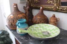 Assortment of items to include two carved African gourds, salad bowl and servers, ceramic jug and bottle
