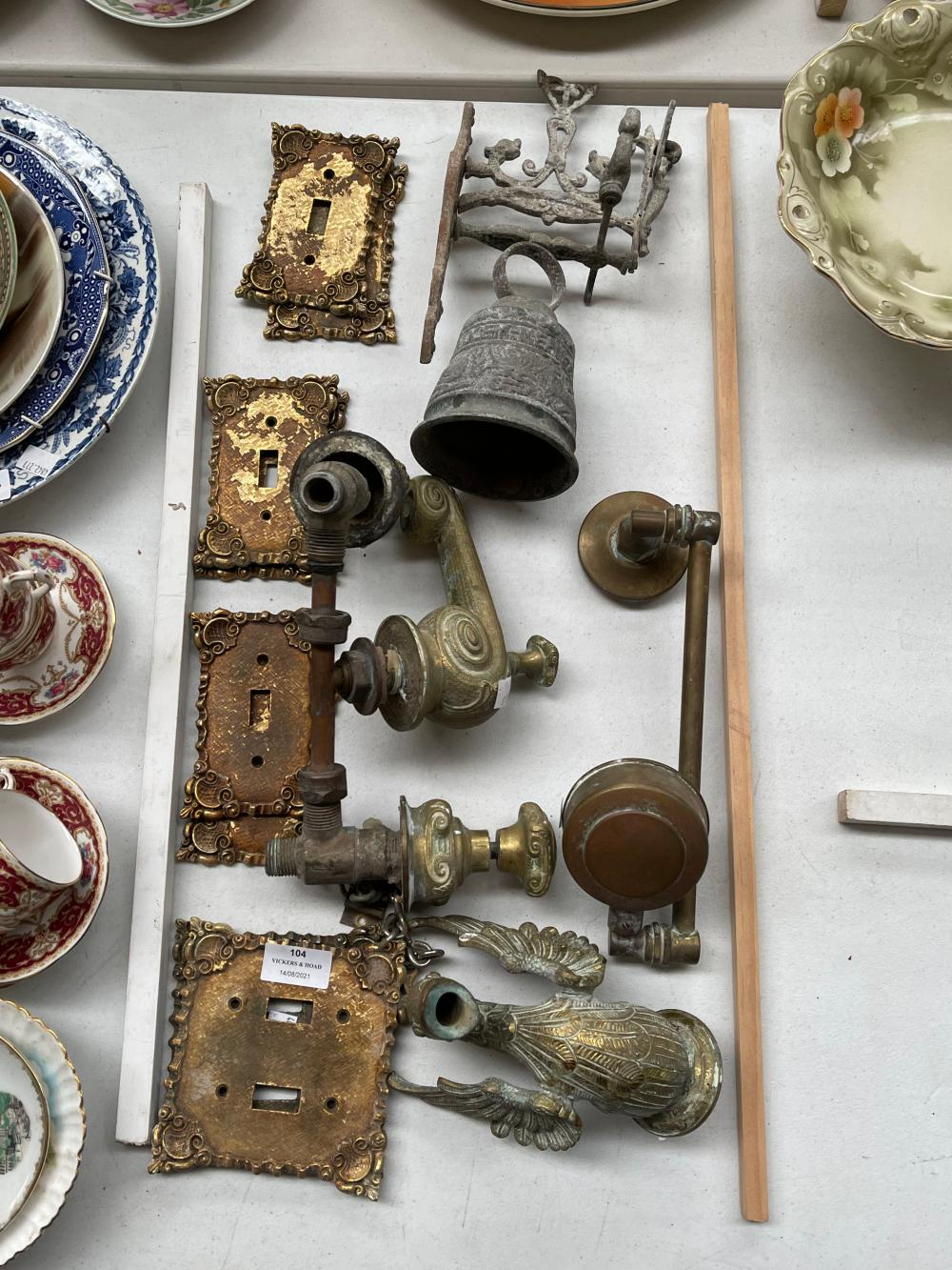 Assortment of cast brass tap fittings, bell & brass switch plates