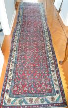 Vintage village weave hand knotted hall runner of red and blue ground, ex Cadrys, approx 455cm x 118cm