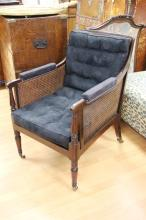 Antique Regency mahogany Bergere circa 1830's with navy upholstery, turned supports and legs, terminating with brass capped castors