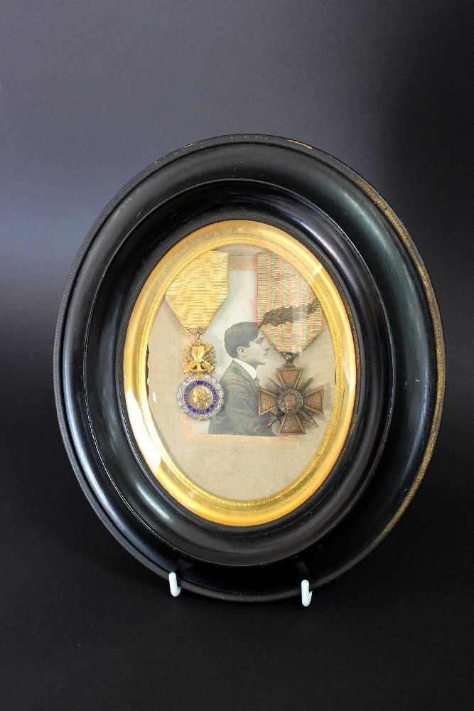Antique French pair of WWI military medals in an oval ebonised frame with photograph of recipient, approx 27cm x 23cm including frame