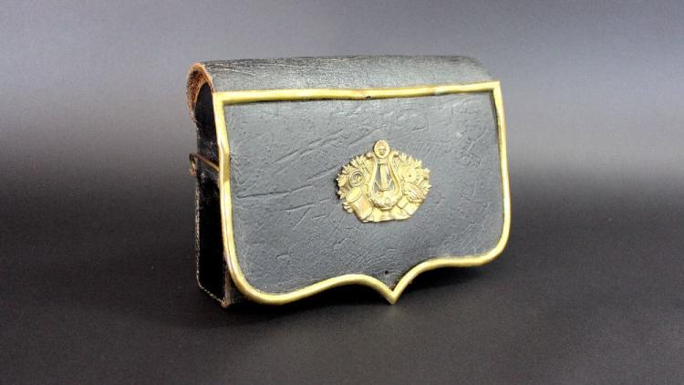 Antique French musician's shoulder belt pouch in black leather covered metal with gilt brass fittings and badge.