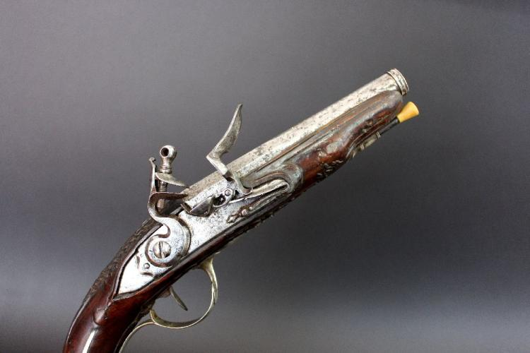 Antique Continental flintlock pistol of good quality, approx 29cm overall with 14cm cannon barrel of about 28 bore. Full stocked with intensive good floral carving. Nickel silver furniture.