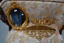 Decorative gold painted lot to include mirror, ornament with putti, a shelf (3)