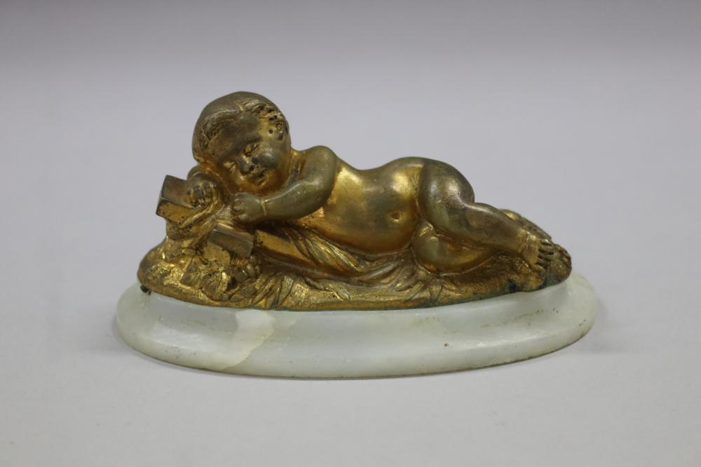 French gilt bronze figure of baby Jesus laying on cross, mounted to alabaster base, unsigned, approx 5cm H x 11.5cm W x 5.5cm D