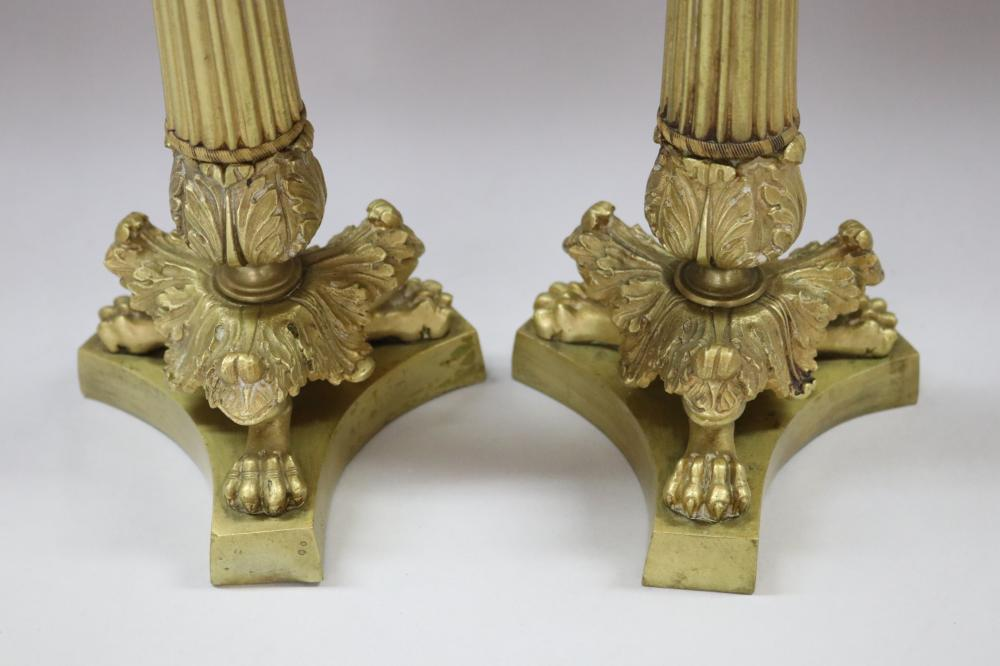 Pair of antique French Empire style gilt candlesticks, having lion paw feet and fluted columns, each approx 28cm H (2)