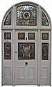 A Monumental stained glass door and surround, the