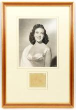 A waist length studio photographic portrait of Linda Darnell, mounted and f