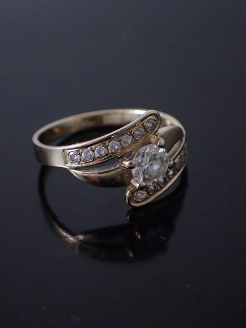 A diamond set solitaire ring set in 18ct gold with gem set shoulders