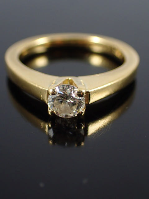 An 18ct gold diamond solitaire ring with a copy of a valuation which states the piece is 0.35cts, H
