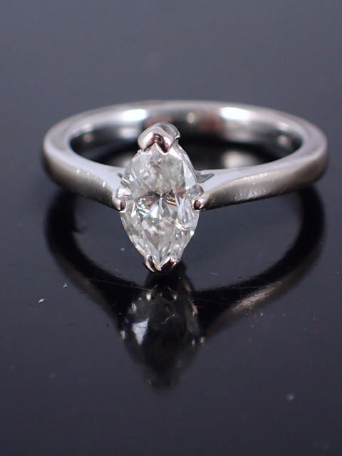 A diamond marquise cut ring, with a valuation which states the diamond is 0.91cts, colour G/H, clari