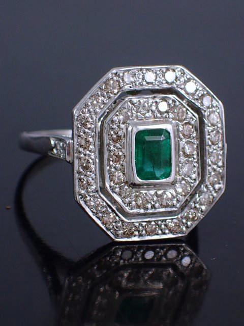 A diamond & emerald cluster ring