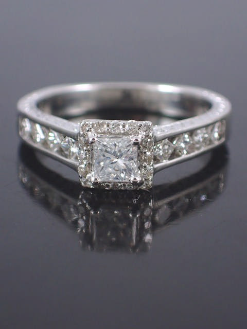 A diamond solitaire ring set with diamond shoulders