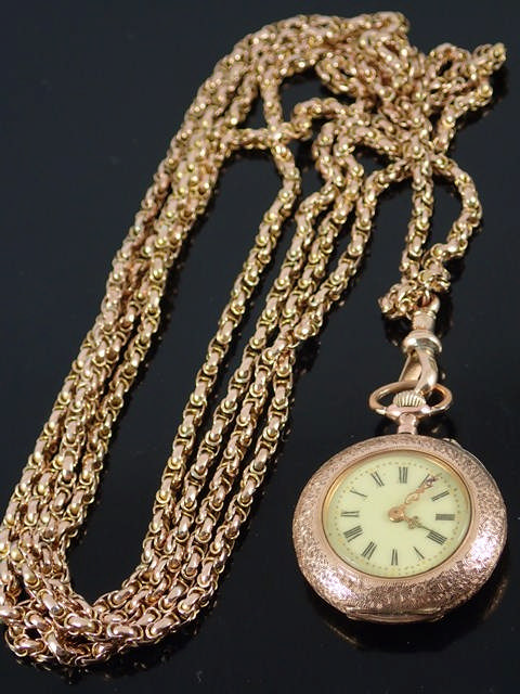 A 62 inch gold muff chain with gold fob watch