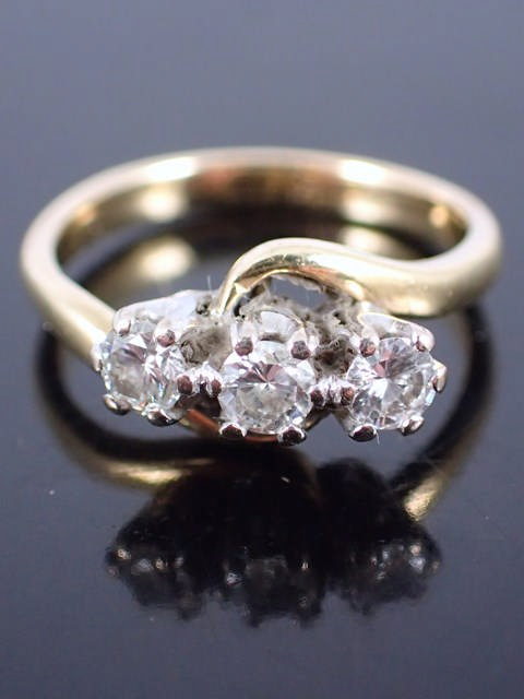A gold set diamond three stone ring
