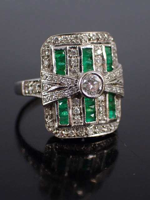 A diamond & emerald cluster ring