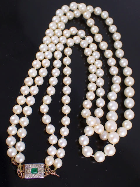 A double row pearl necklace set with a diamond & emerald encrusted clasp. Approx. 18.5 inches in len