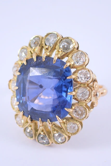 A fine antique Ceylon sapphire & diamond cluster ring, the sapphire is estimated as 14.70cts, with a