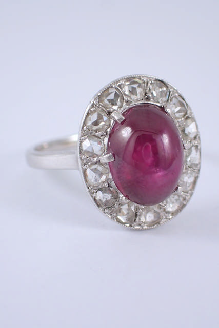 A cabochon ruby & diamond cluster ring