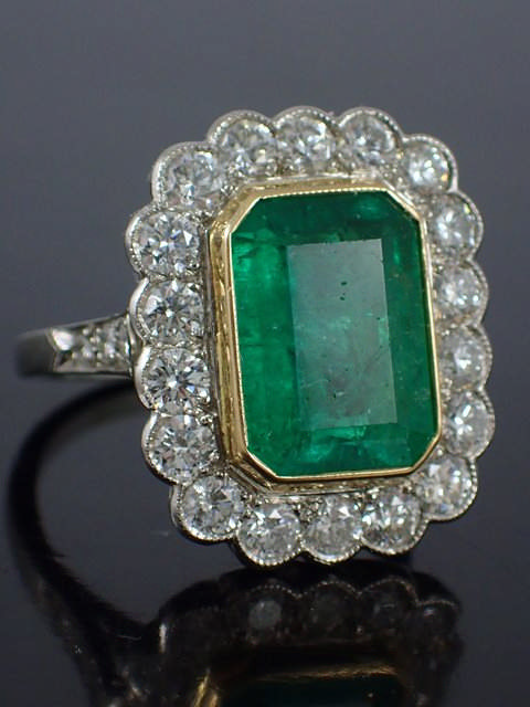 An emerald & diamond cluster ring the estimated weight of emerald is 6cts & estimated total diamonds
