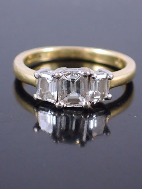 A diamond three stone ring set in 18ct gold, with a copy of a valuation from Diamant which states th