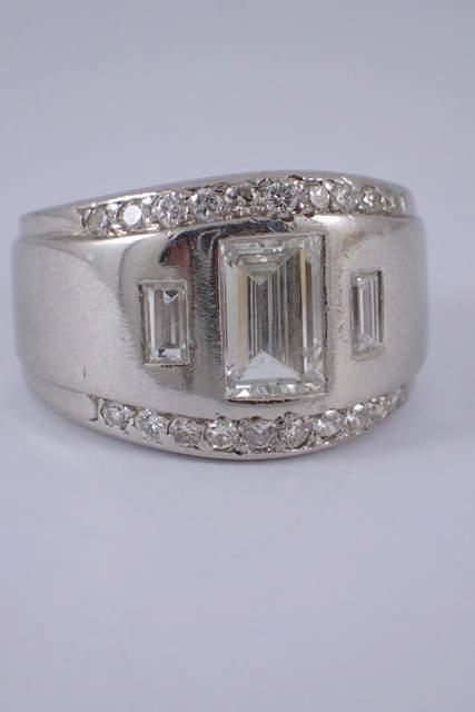 A platinum diamond three stone ring set with diamond surround, total estimated weight of diamonds 1.