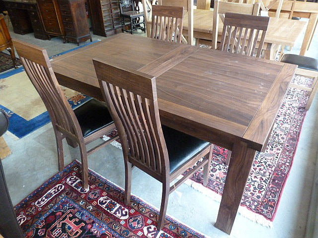 A dark wood extending dining table with one