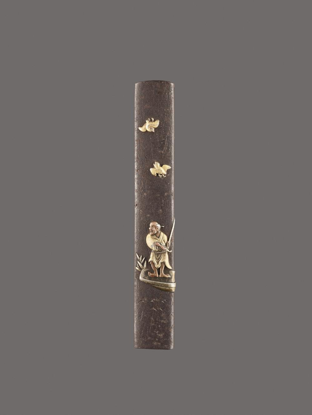 A MIXED METAL KOZUKA HANDLE DEPICTING A FISHERMAN IN A BOAT AND BIRDS