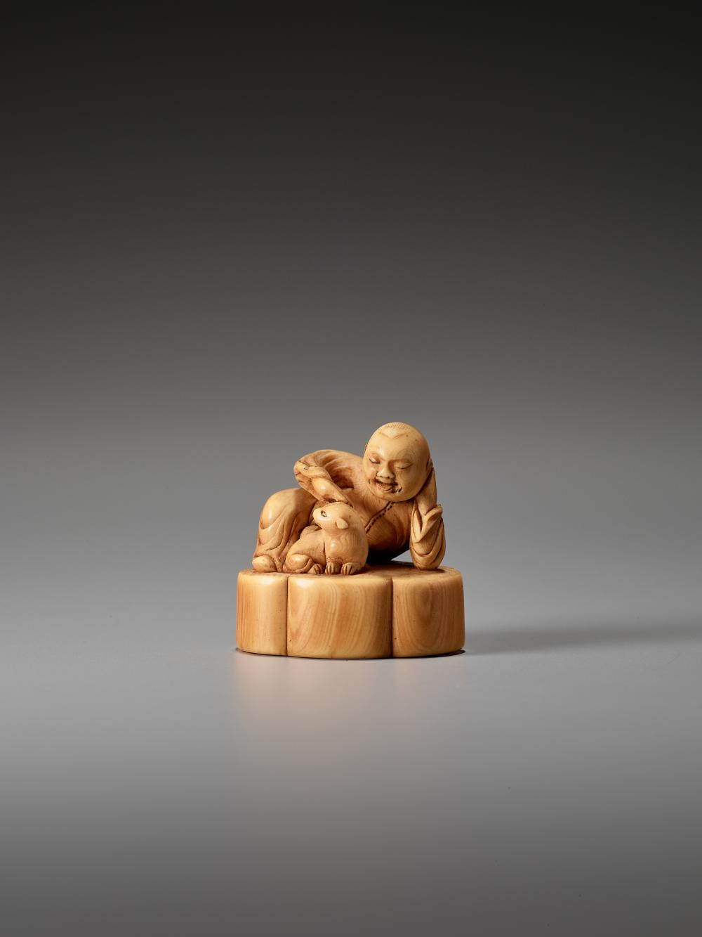 A FINE AND EARLY IVORY NETSUKE OF A CHINESE BOY WITH DOG
