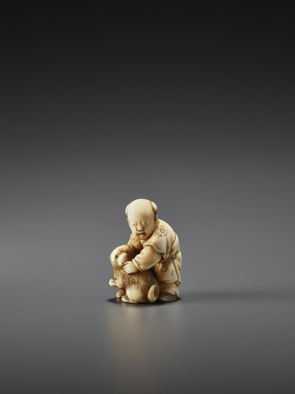 AN IVORY NETSUKE OF A CHINESE BOY WITH PUPPY BY TOMOCHIKA
