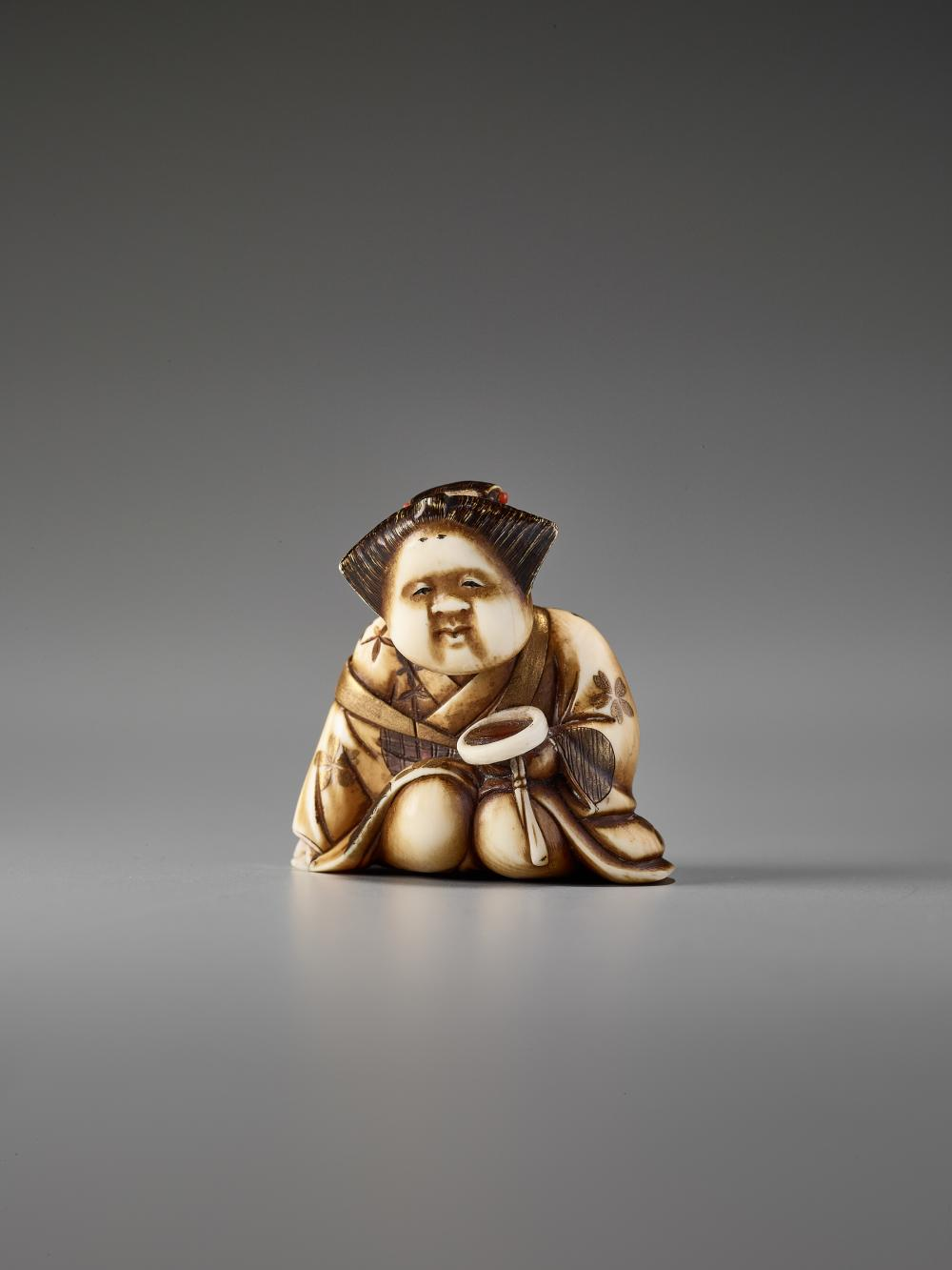 AN IVORY AND LACQUER NETSUKE OF OKAME WITH A SAKE CUP BY KEIMIN