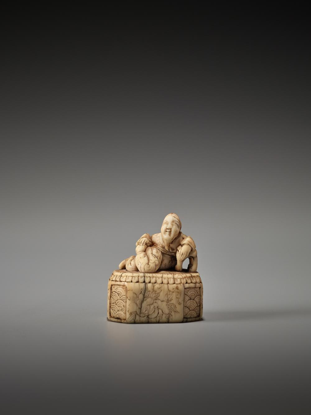 AN EARLY IVORY NETSUKE DEPICTING A CHINESE SAGE ON A DECORATED BASE