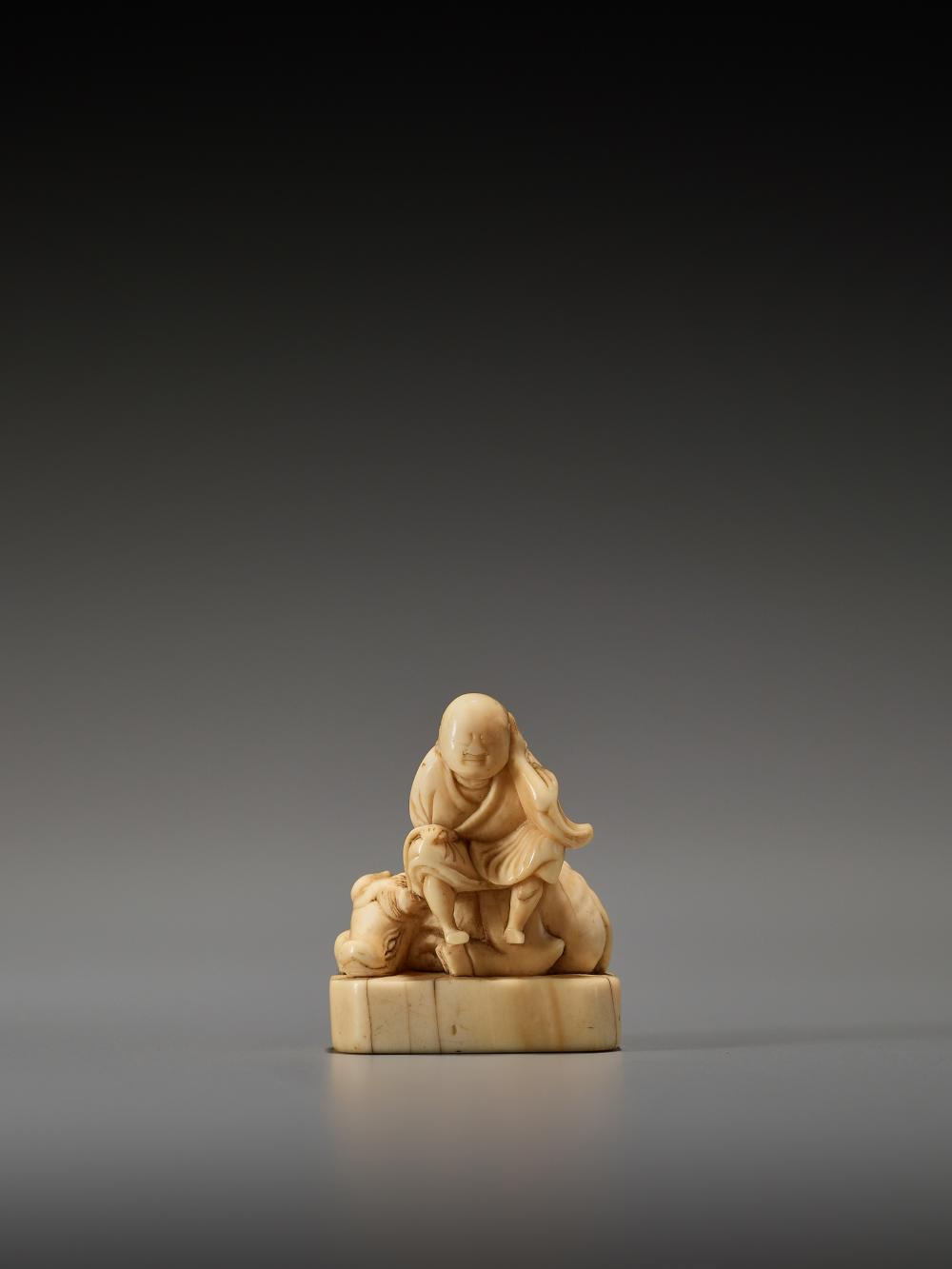 AN EARLY IVORY NETSUKE OF AN OX HERDER