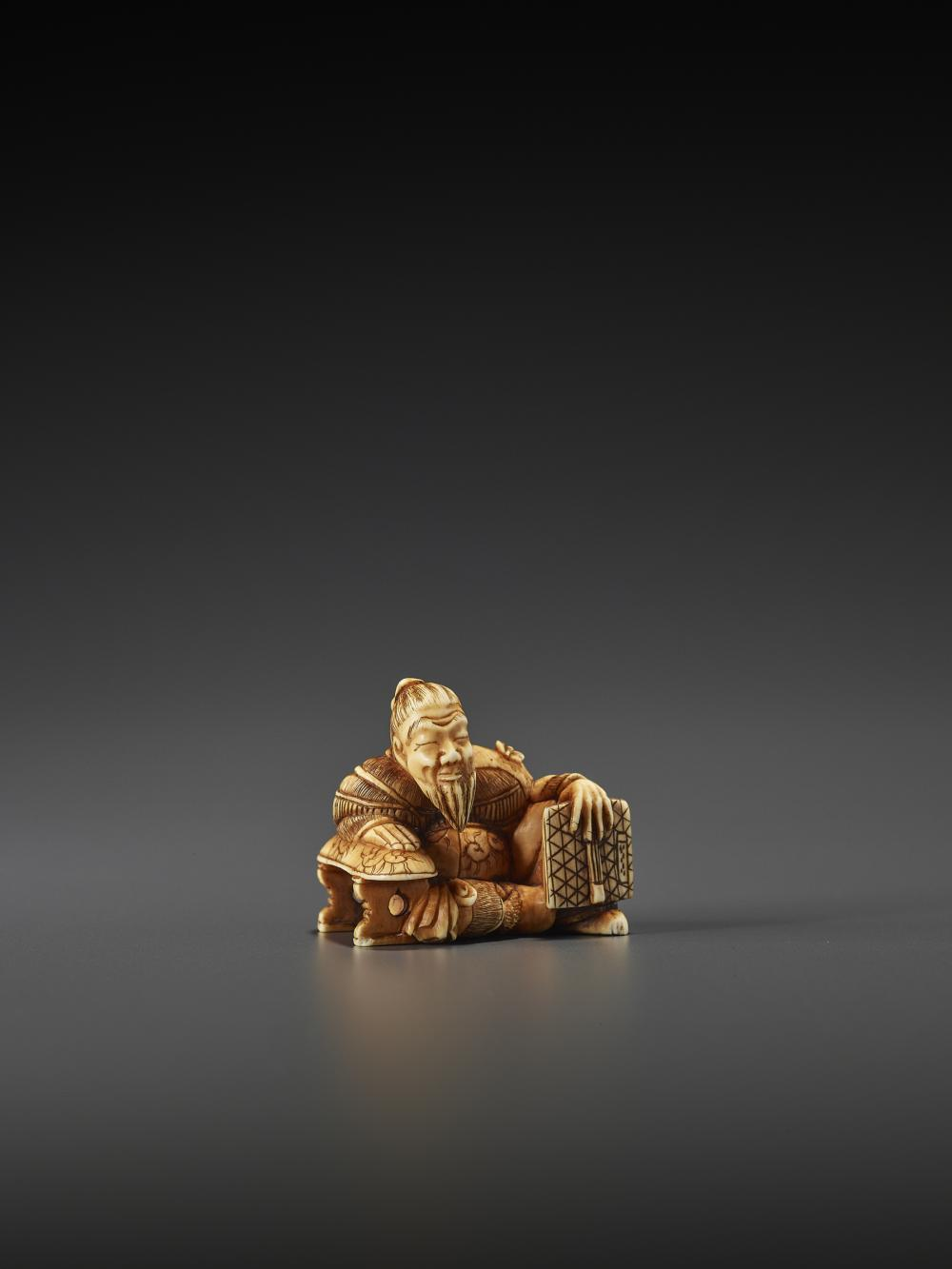 A FINE IVORY NETSUKE OF A COURT OFFICIAL