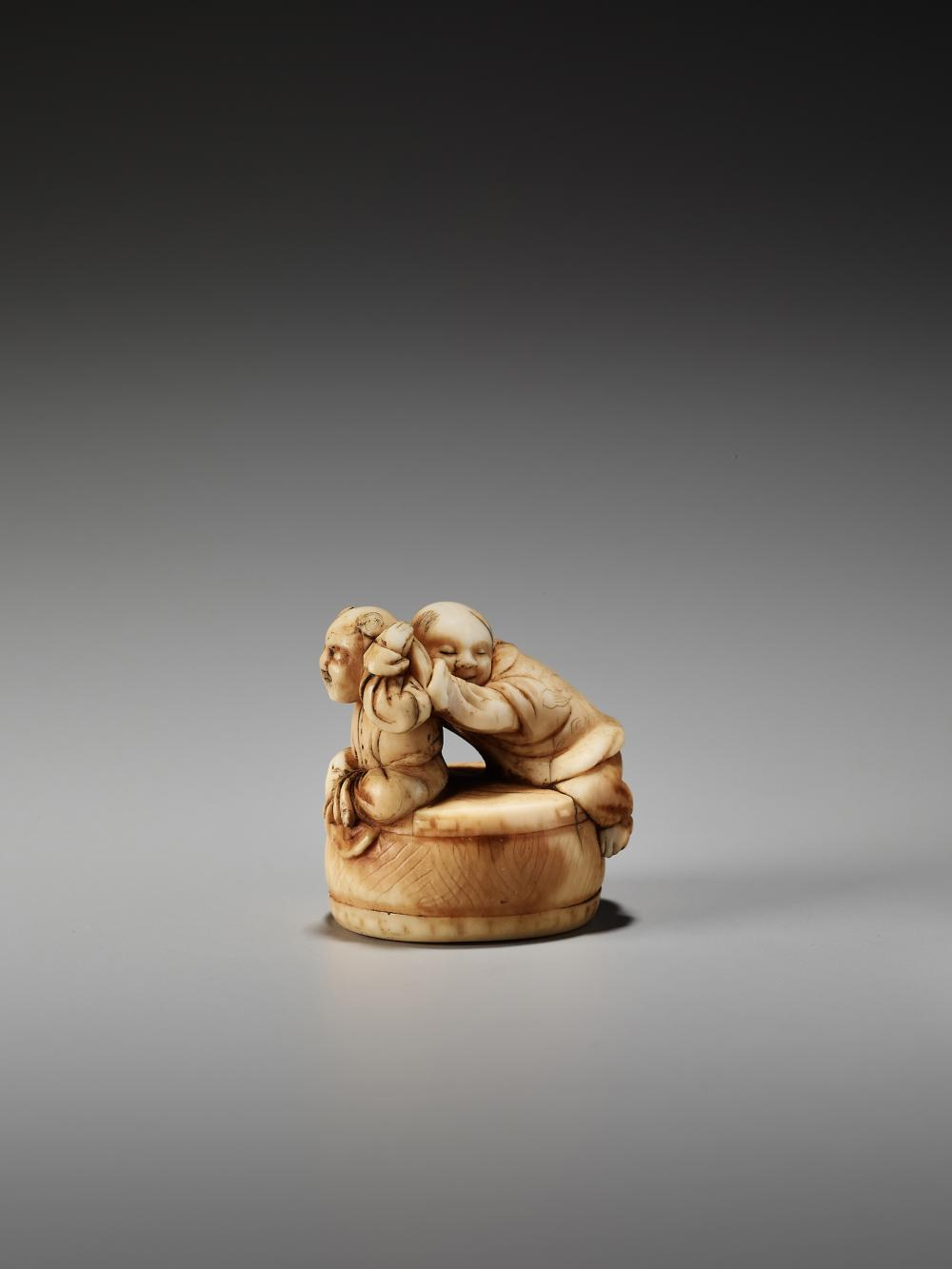 AN EARLY IVORY NETSUKE OF TWO BOYS ON A DRUM