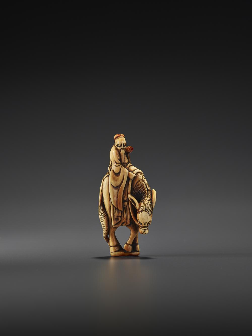 AN EARLY IVORY SEAL NETSUKE OF TOBA ON A MULE