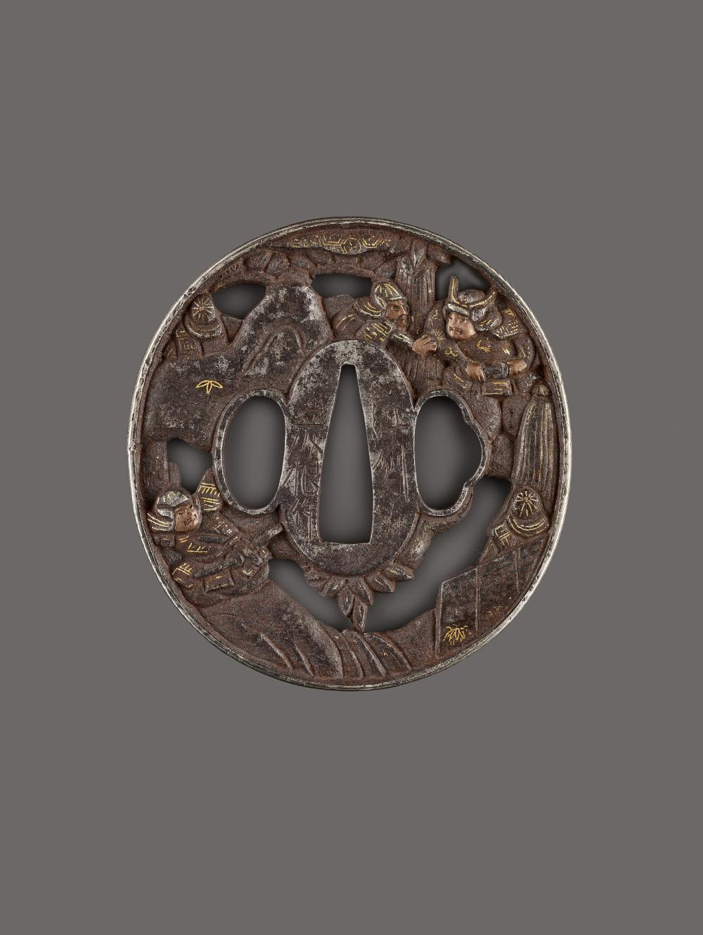 AN IRON, COPPER AND GOLD TSUBA DEPICTING SAMURAI WARRIORS AMID ROCKS BY GENKO